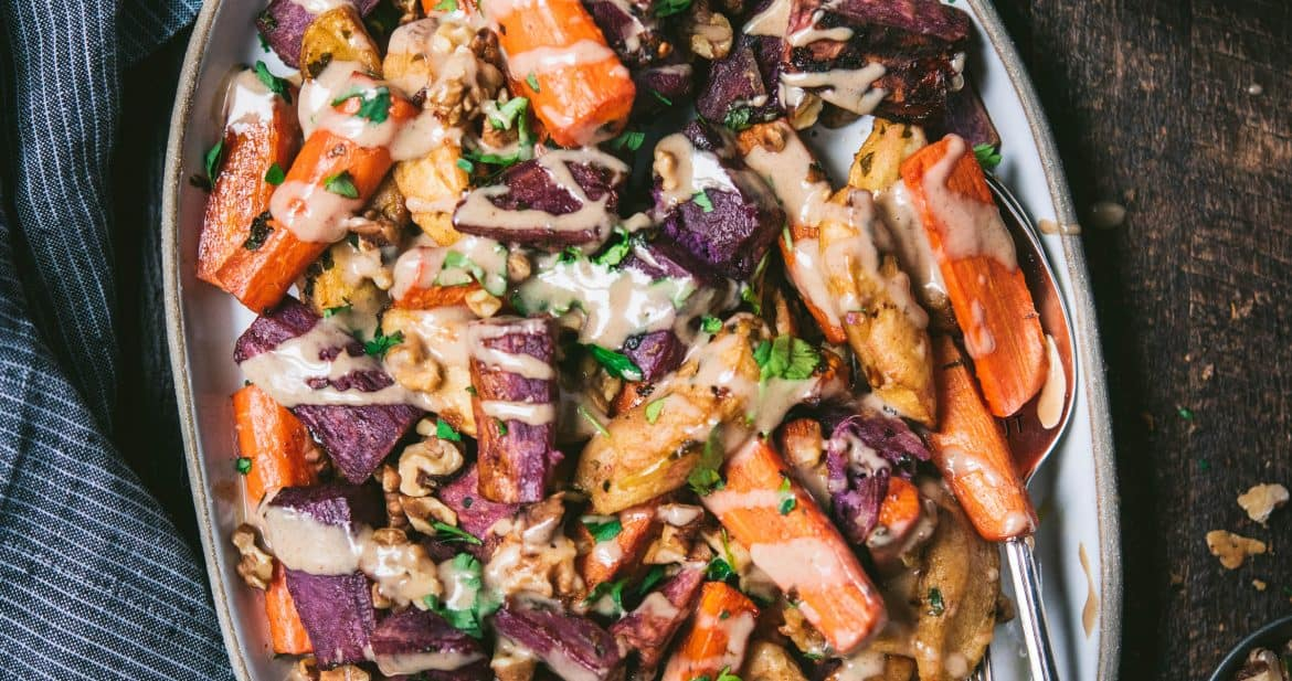 Roast carrots, purple potatoes and apples with cinnamon tahini on a white tray with blue linen