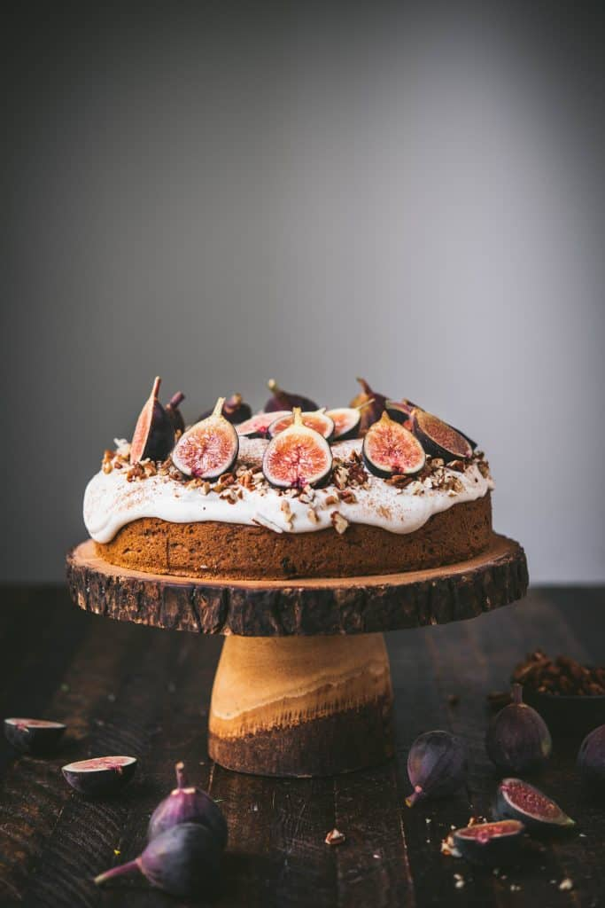 Side view of carrot cake with cream cheese frosting and fresh figs on a wooden cake stand