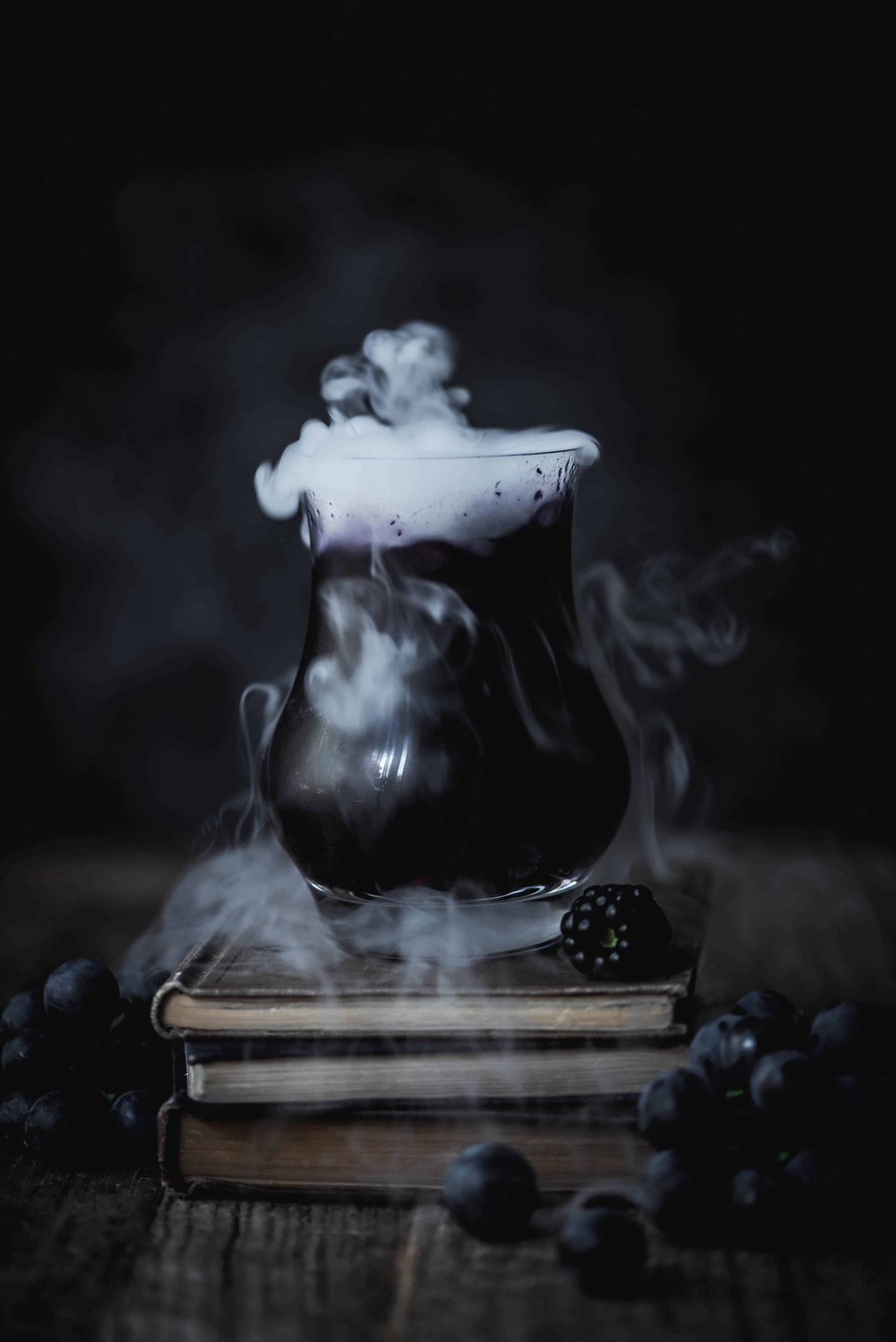 Black and purple halloween cocktail on a stack of old books with dry ice coming out of top