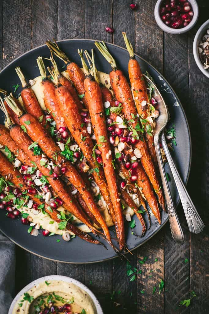 Close up of harissa roasted carrots over pumpkin hummus on a gray plate