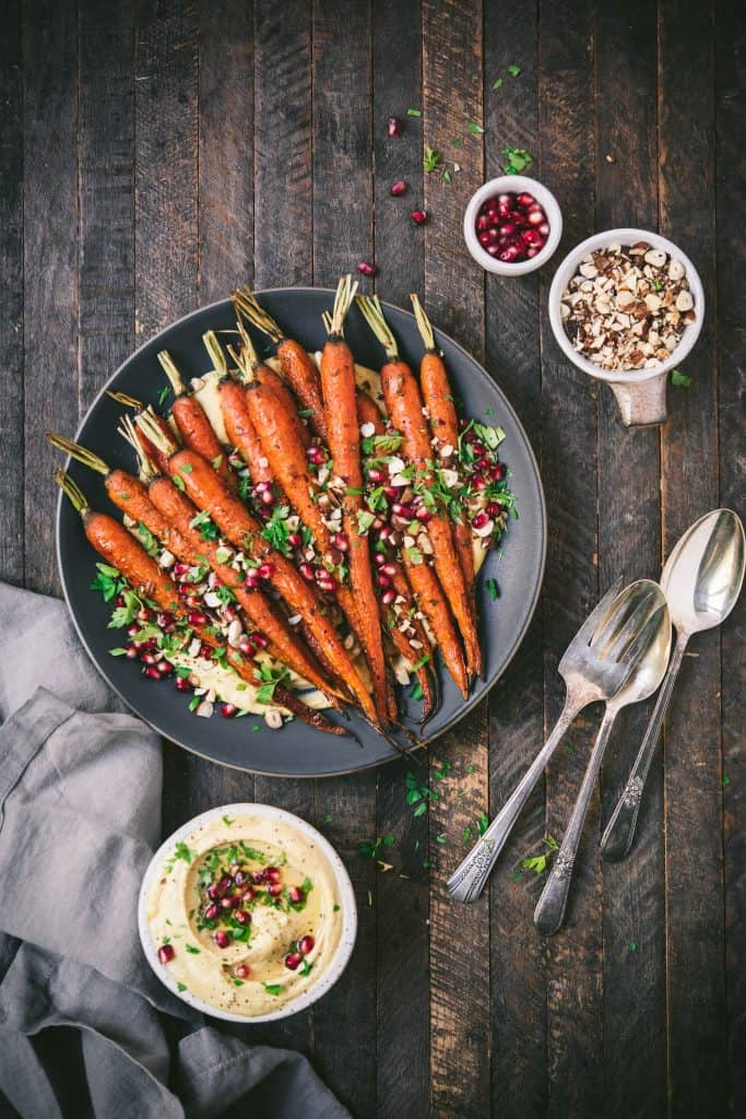 Overhead of harissa roasted carrots over a bed of creamy pumpkin hummus on a gray plate on wood background