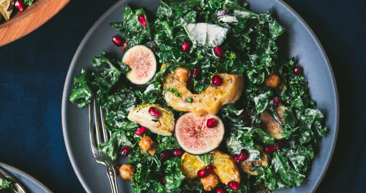 Overhead of kale salad with roasted vegetables and tahini dressing on a gray plate