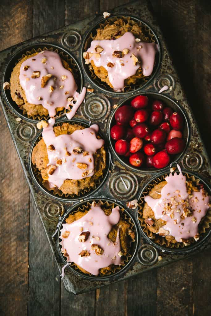 Overhead of cranberry apple muffins with pink cranberry glaze in an antique muffin tray