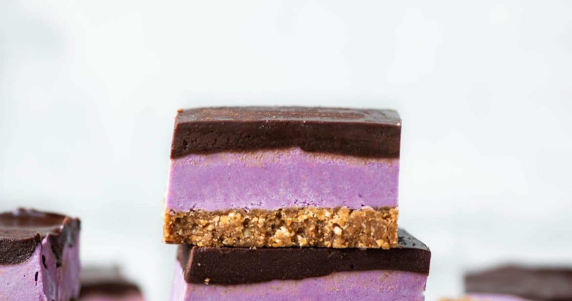 Stack of purple sweet potato cheesecake bars with chocolate ganache on white background
