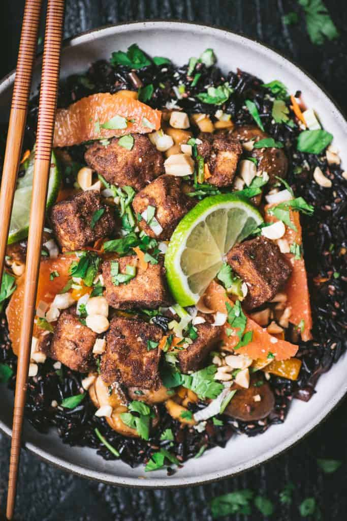 Close up of black rice with veggies and five spice tofu in a bowl with chopsticks