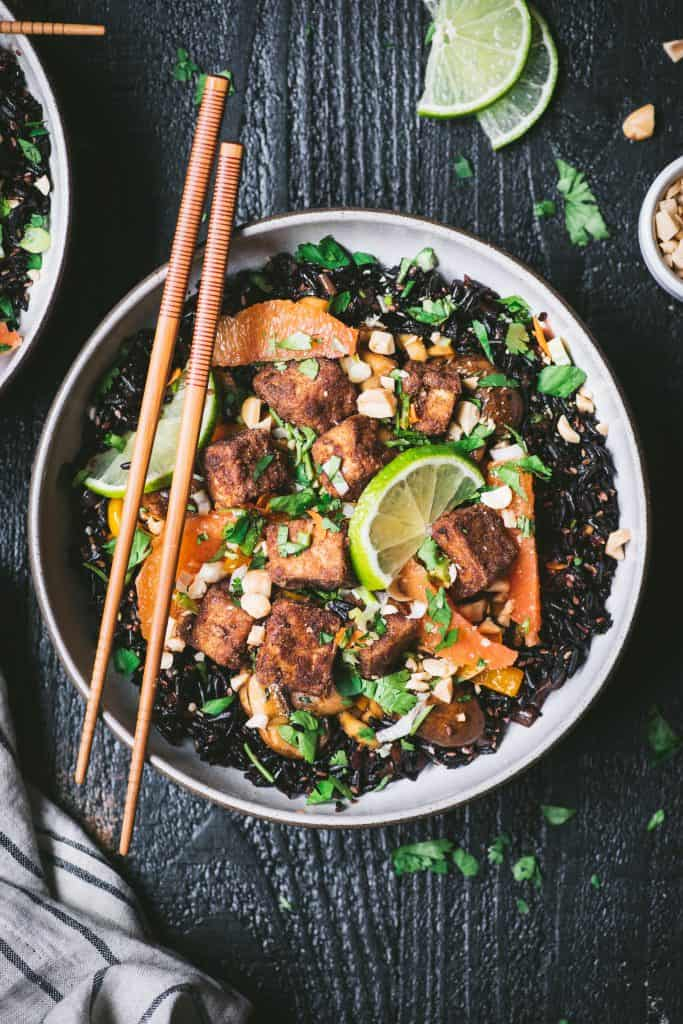 Overhead of black rice and five spice crispy tofu in a white bowl with chopsticks