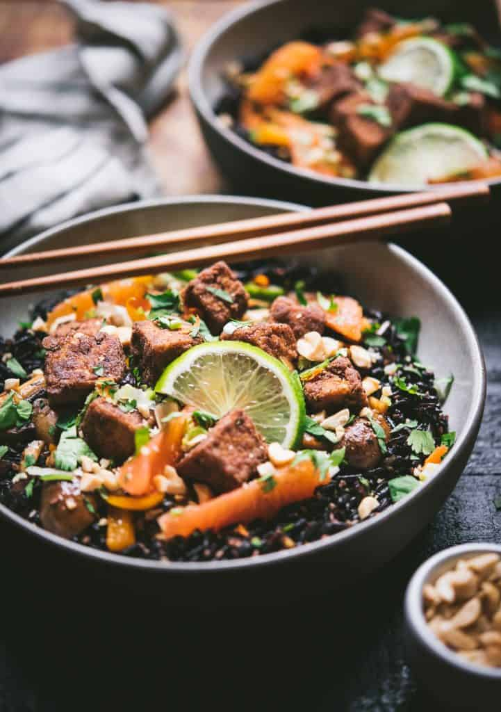 45 degree view of black rice with veggies and five spice tofu in a bowl with chopsticks