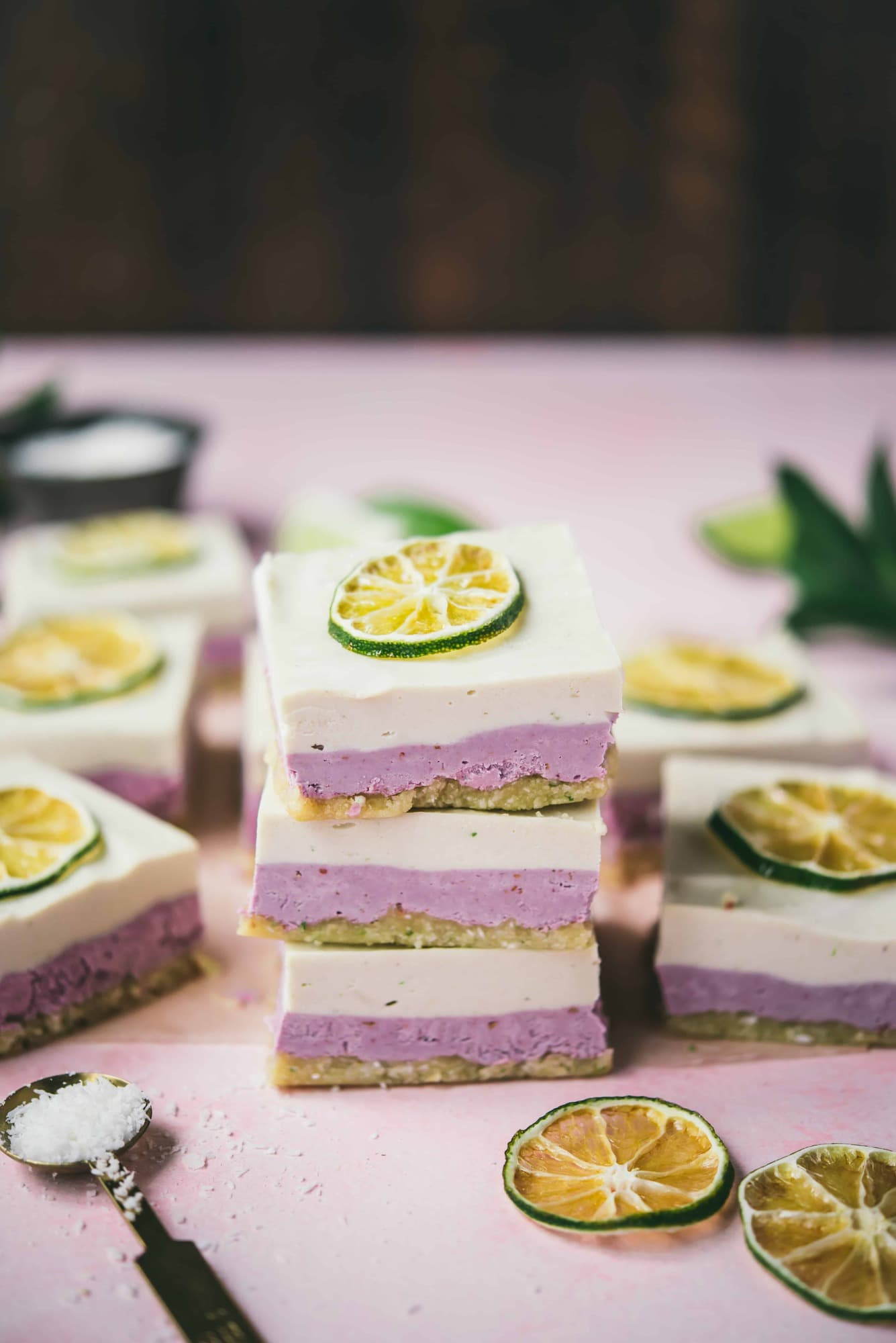 Three stacked coconut lime raspberry cheesecake bars on a pink background
