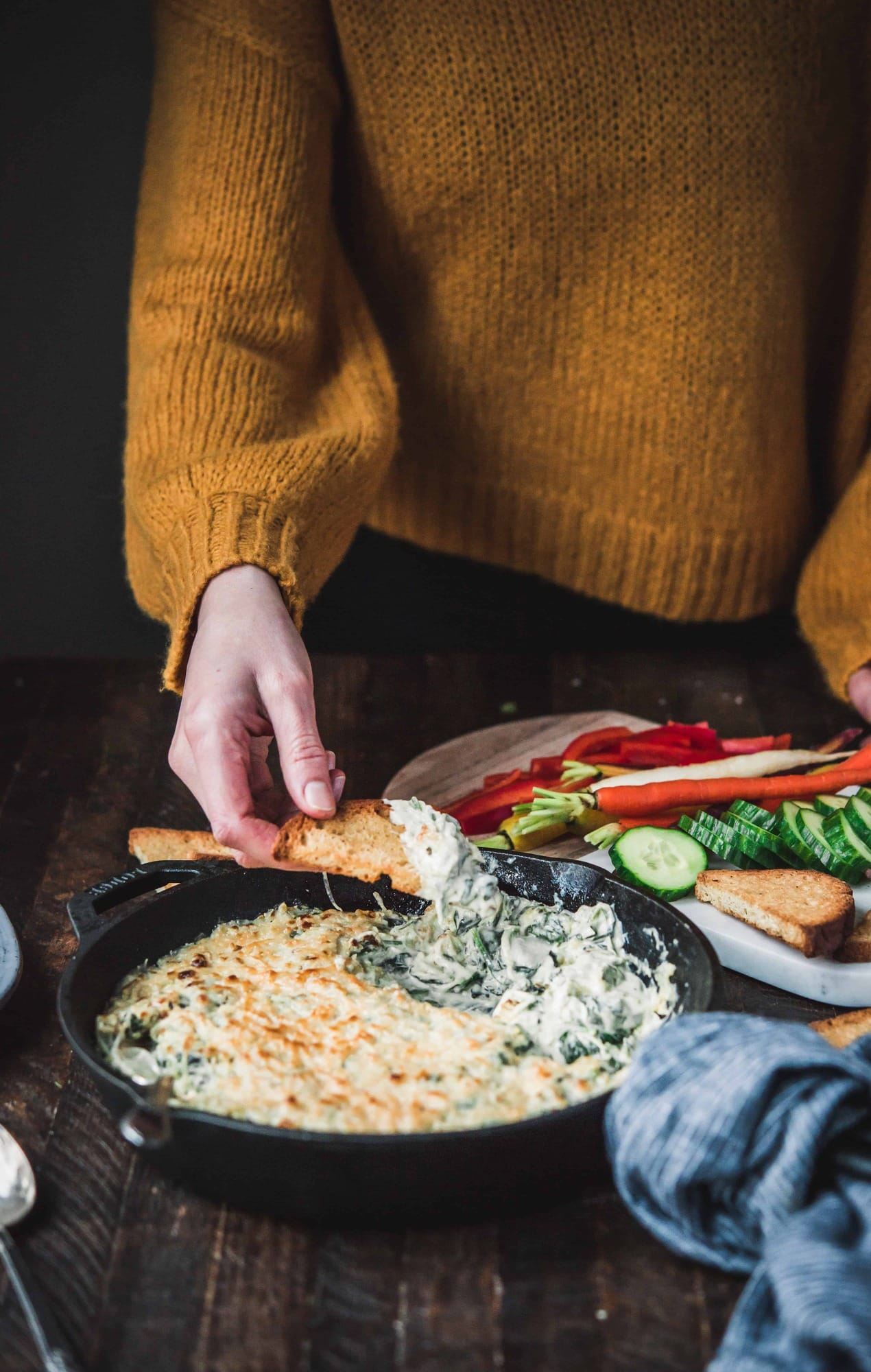 Side view of person in sweater dipping bread into vegan spinach artichoke dip in cast iron skillet