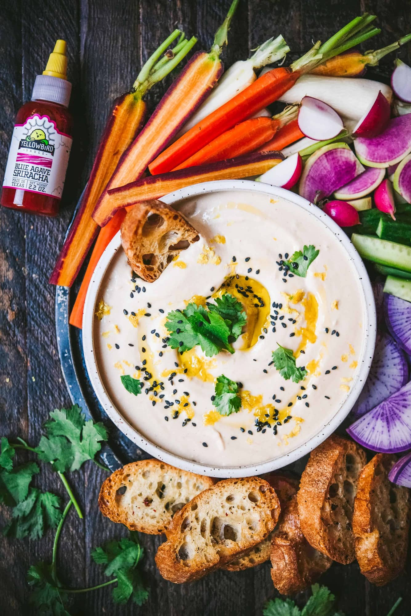 Overhead of White Bean Dip with toasted bread and colorful vegetables