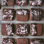 Overhead of chocolate dipped peppermint shortbread cookies on a cooling rack