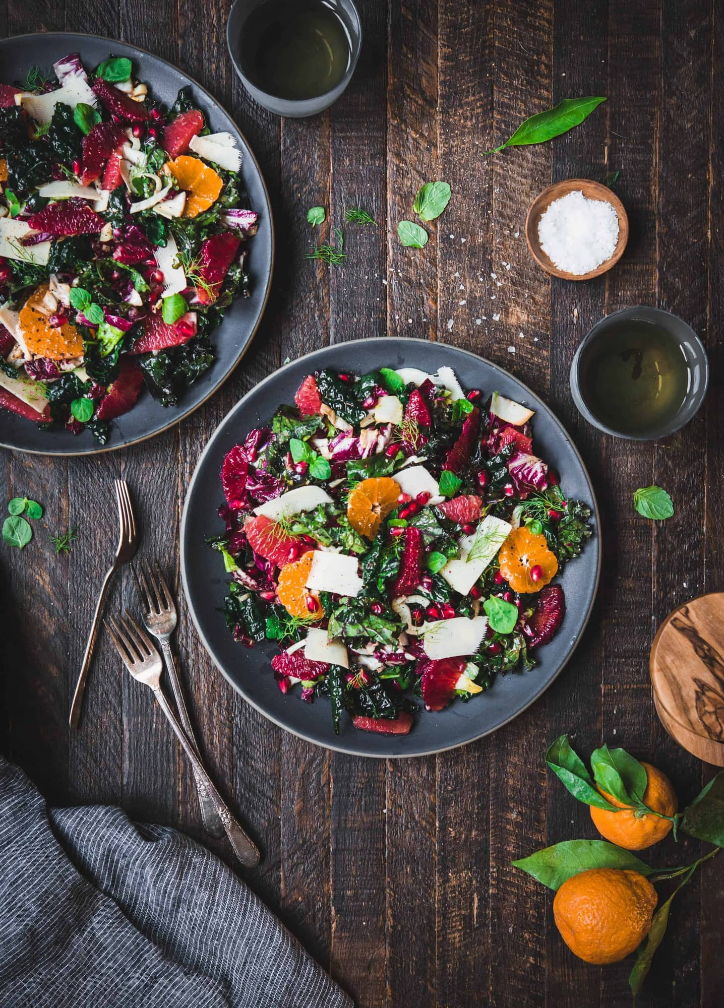 Overhead shot of beautiful winter greens and citrus salad on rustic wood background