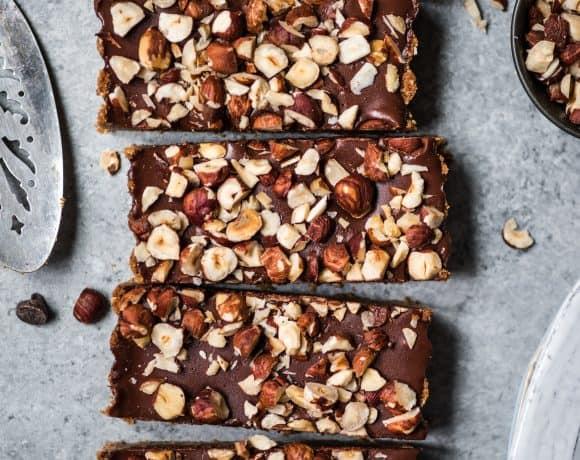 Overhead of vegan dark chocolate hazelnut ganache tart with crushed hazelnuts