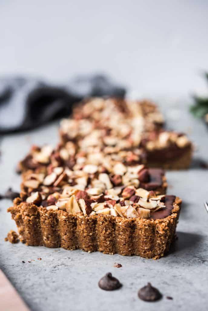 Side view of chocolate hazelnut tart with graham cracker crust
