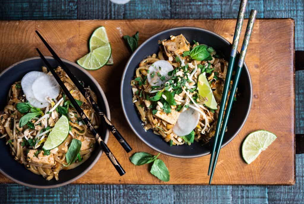 Two bowls of vegan pad thai with chopsticks on rustic wood background