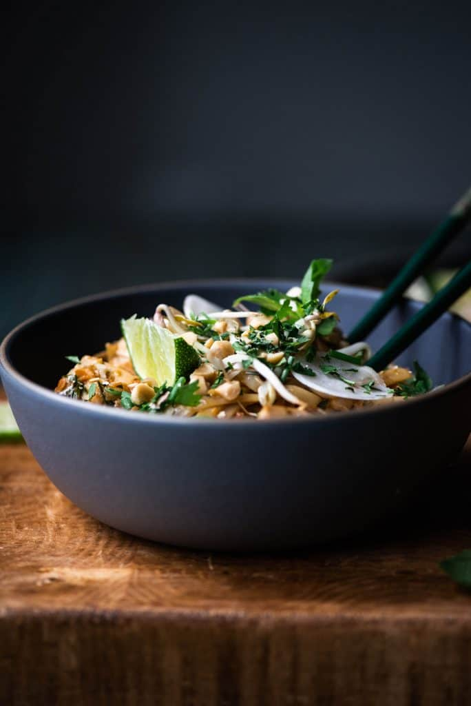 Close up side view of vegan pad thai in dark bowl with fresh herbs