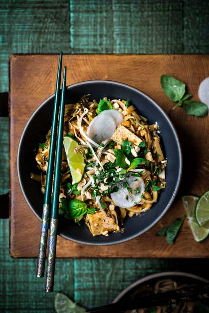 Overhead of vegan pad thai with chopsticks on rustic wood background