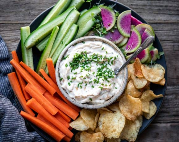 Overhead of vegan caramelized onion dip with vegetables on wood table