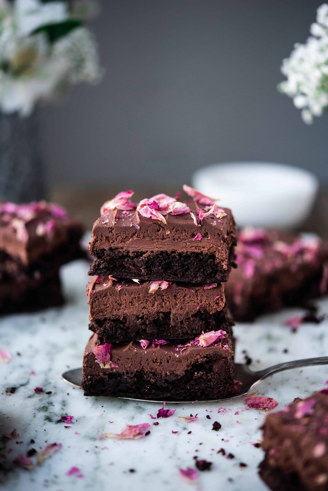 Side view of three stacked chocolate ganache brownies with rose petals on white marble