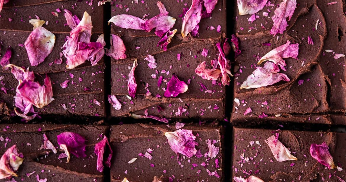 Overhead close up of chocolate ganache frosting brownies with rose petals