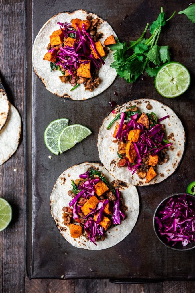 Overhead view of vegan lentil walnut tacos with roasted sweet potatoes, and cabbage on an antique serving tray