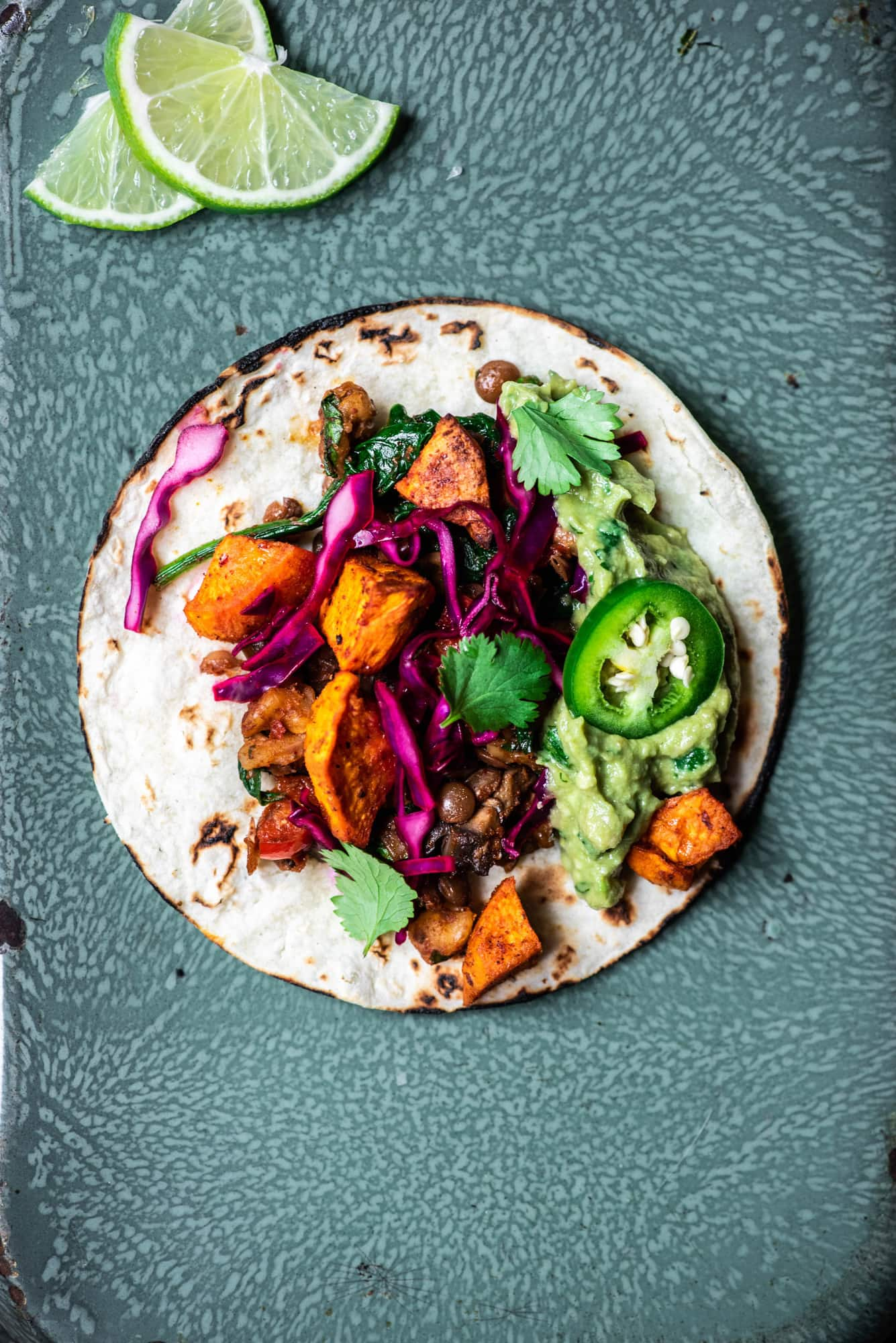 Overhead view of vegan lentil walnut tacos with roasted sweet potatoes, cabbage and guacamole on an antique serving tray