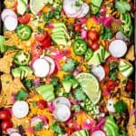 Close up Overhead view of loaded black bean nachos on a sheet pan with avocado, cheese, pickled onion, tomatoes and jalapeño