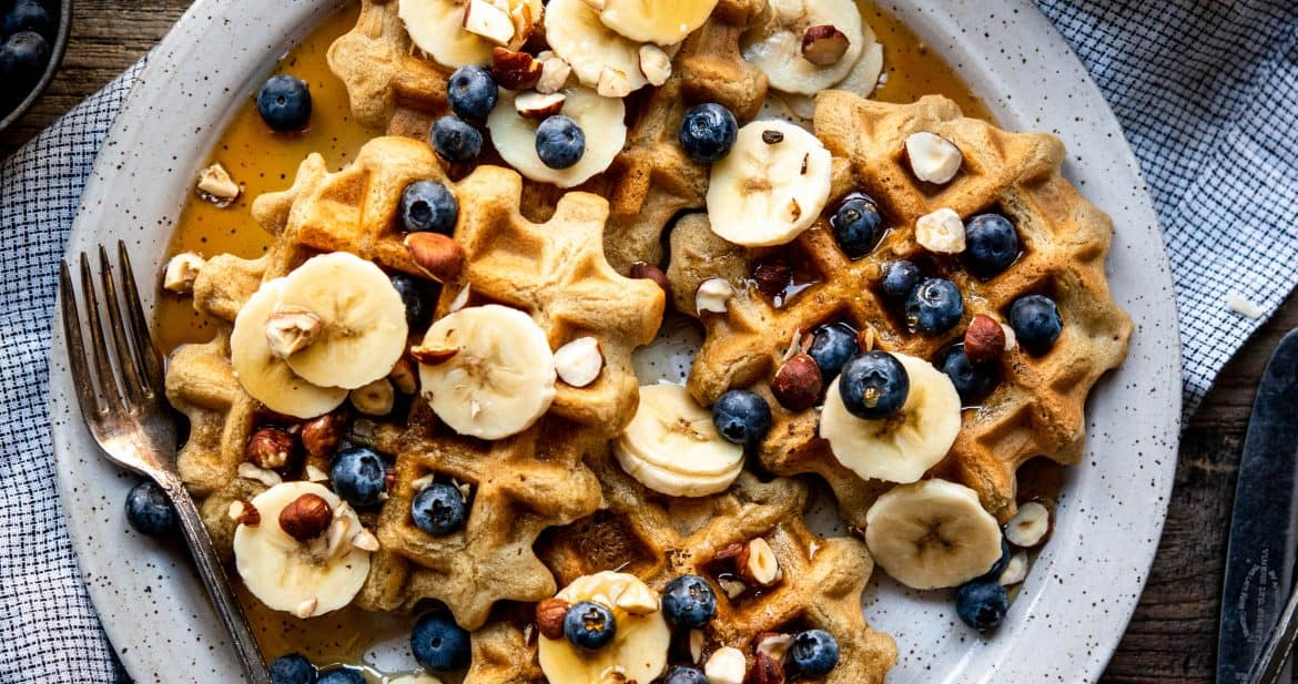 Overhead of waffles topped with sliced bananas, blueberries and maple syrup on a white plate