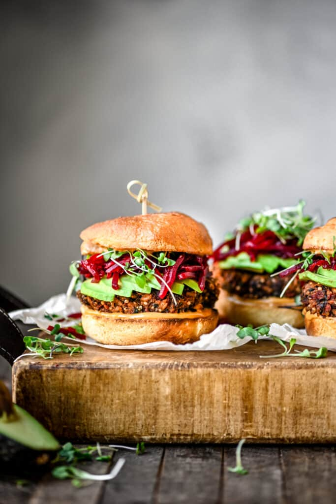 Side view of gluten free veggie burger with smoky shredded beets an avocado