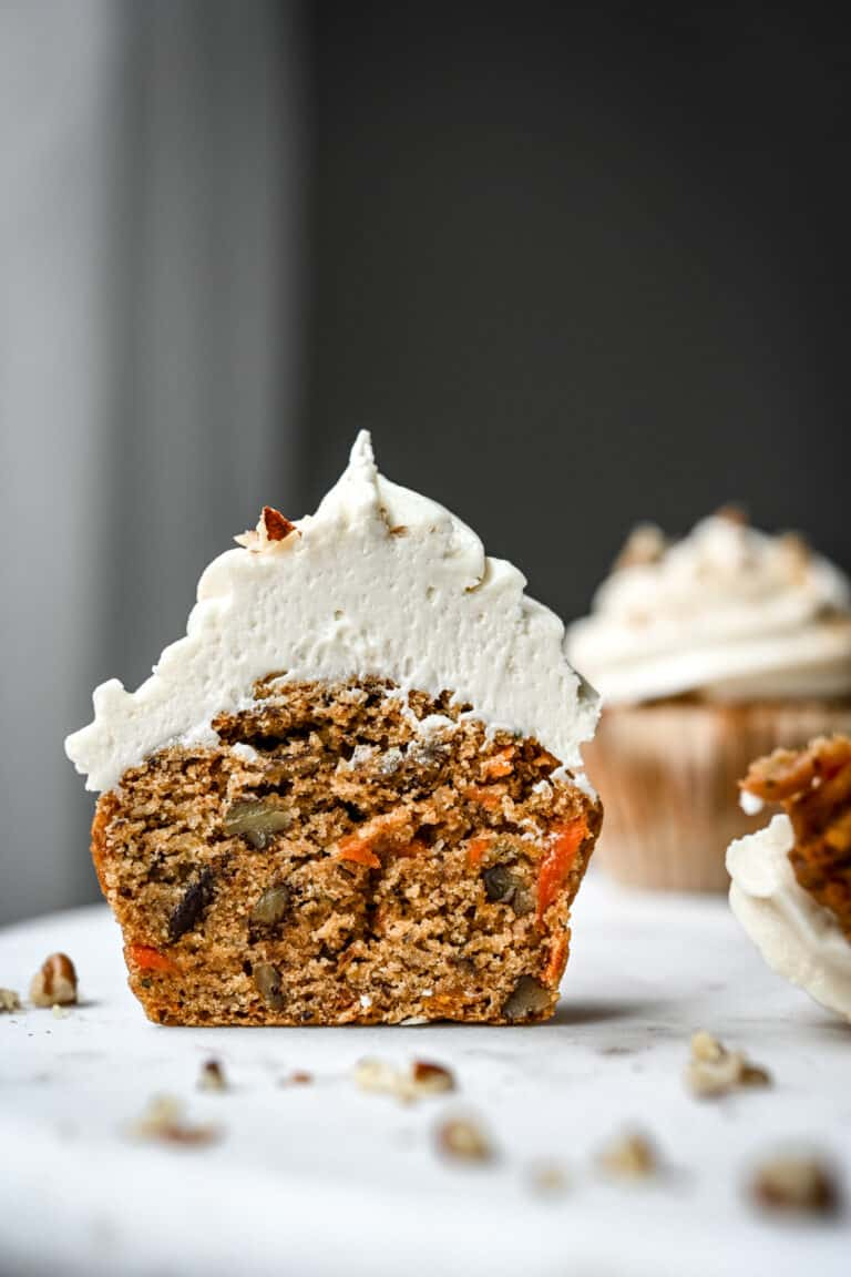 Side view of carrot cake cupcake with cream cheese frosting cut in half
