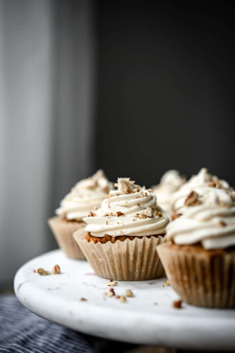 Side view of vegan dessert carrot cake cupcakes with cream cheese frosting on white marble serving platter