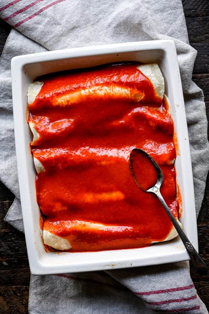Overhead view of vegan enchiladas in a white pan before going in the oven with Mexican enchilada sauce