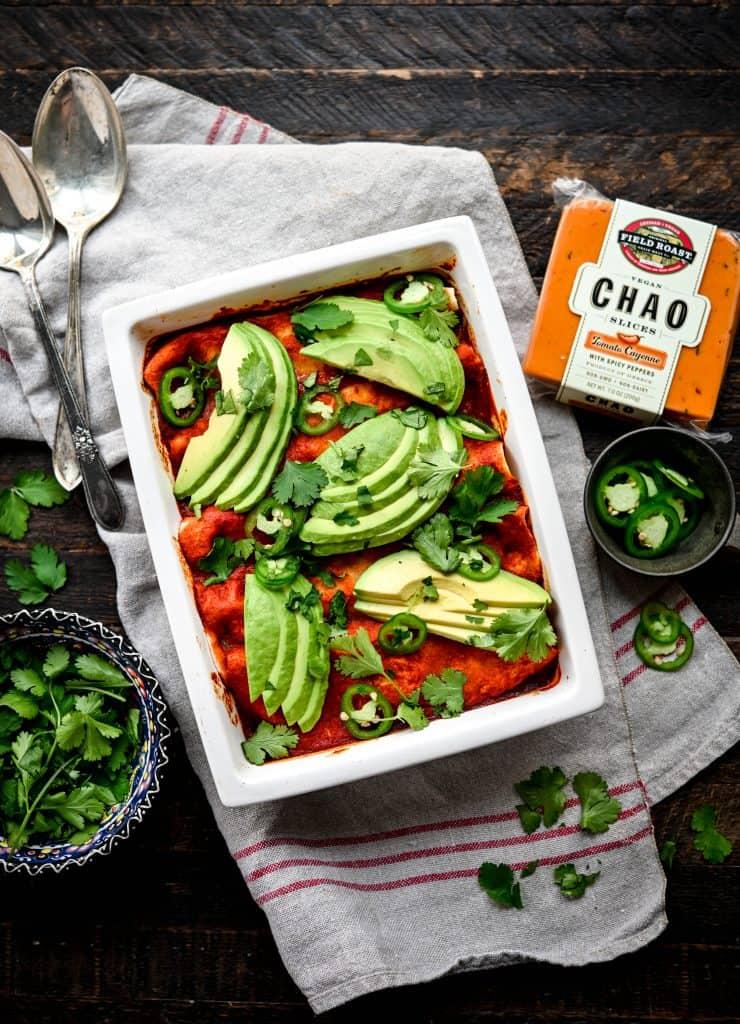 Overhead view of vegan enchiladas in white rectangular pan topped with avocado slices