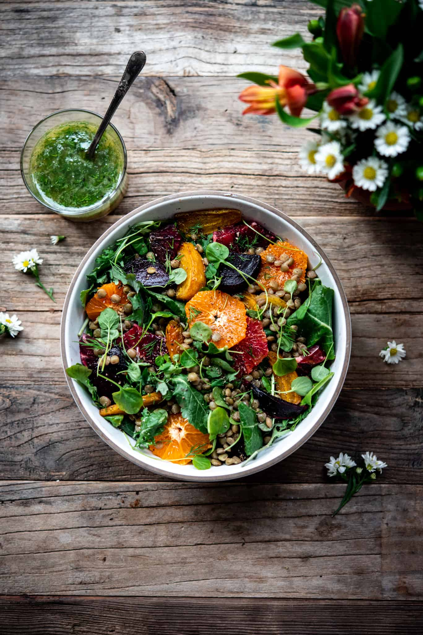 Overhead view of citrus lentil beet salad in a white bowl on a wood table with a vase of flowers