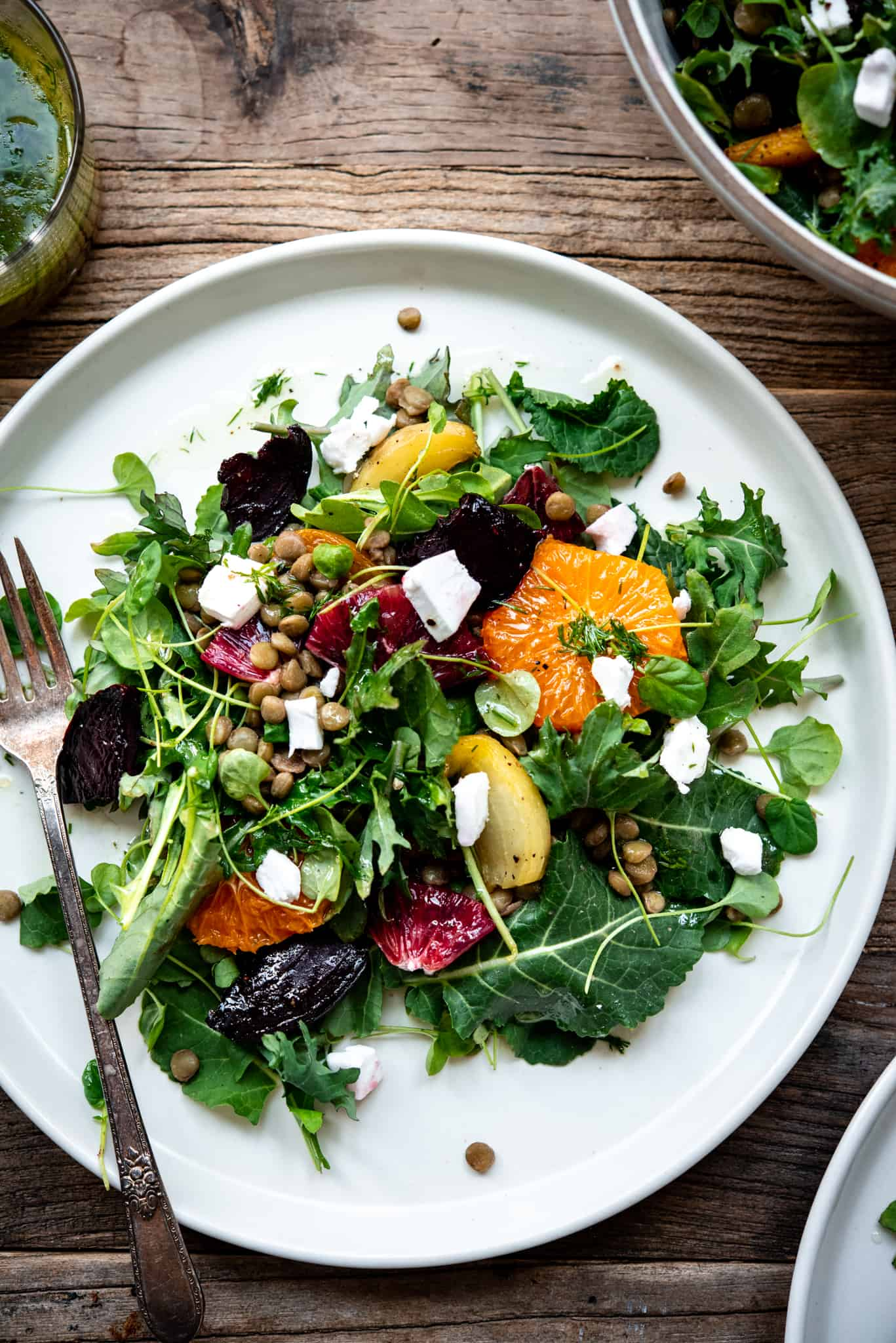 Overhead view of citrus lentil beet salad on a large white plate with a fork on a wood table