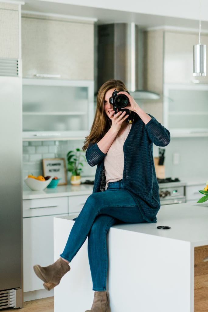 Crowded Kitchen headshot - Lexi holding camera and sitting on counter