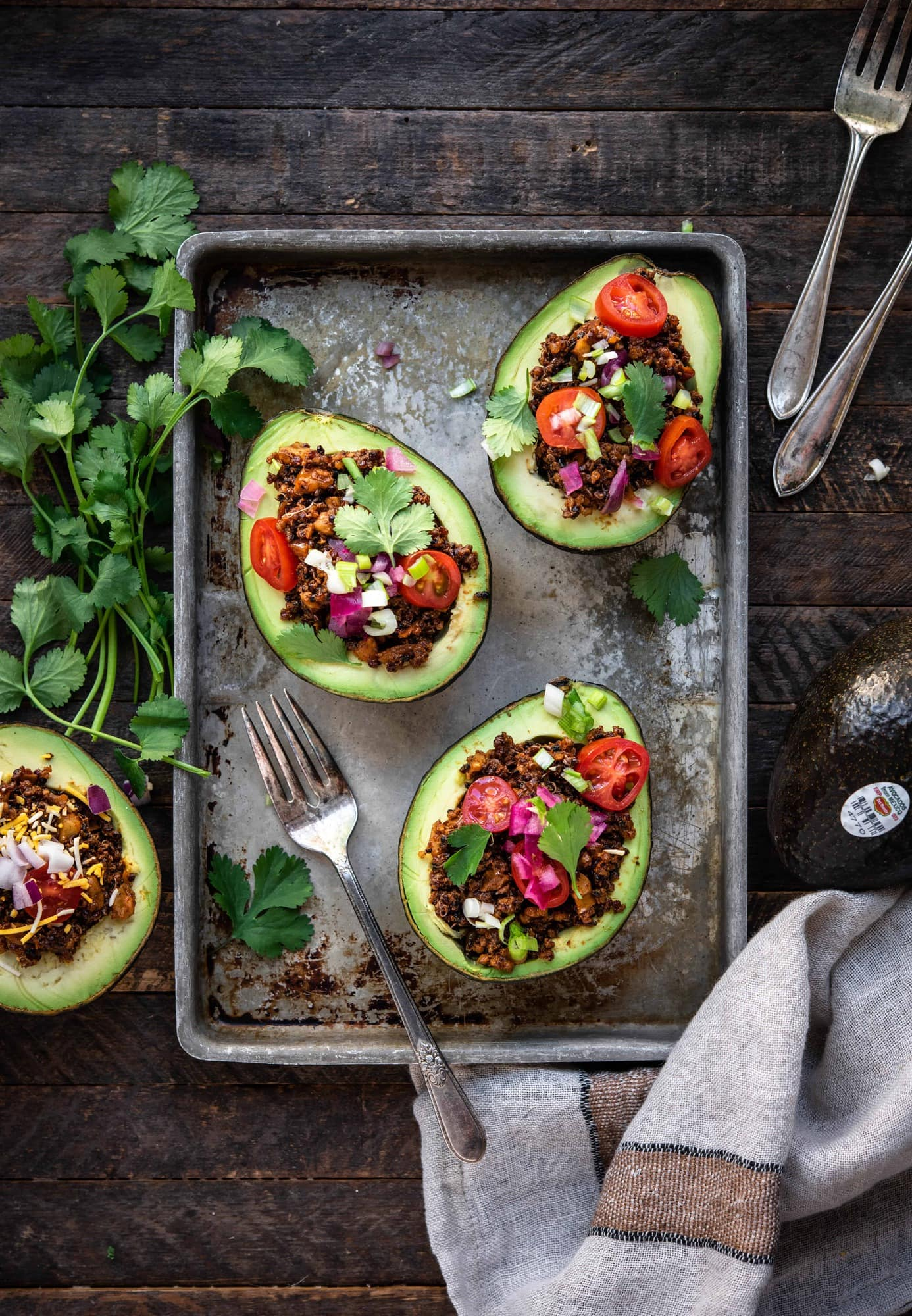Overhead view of vegan taco stuffed avocados on a sheet pan on wood background