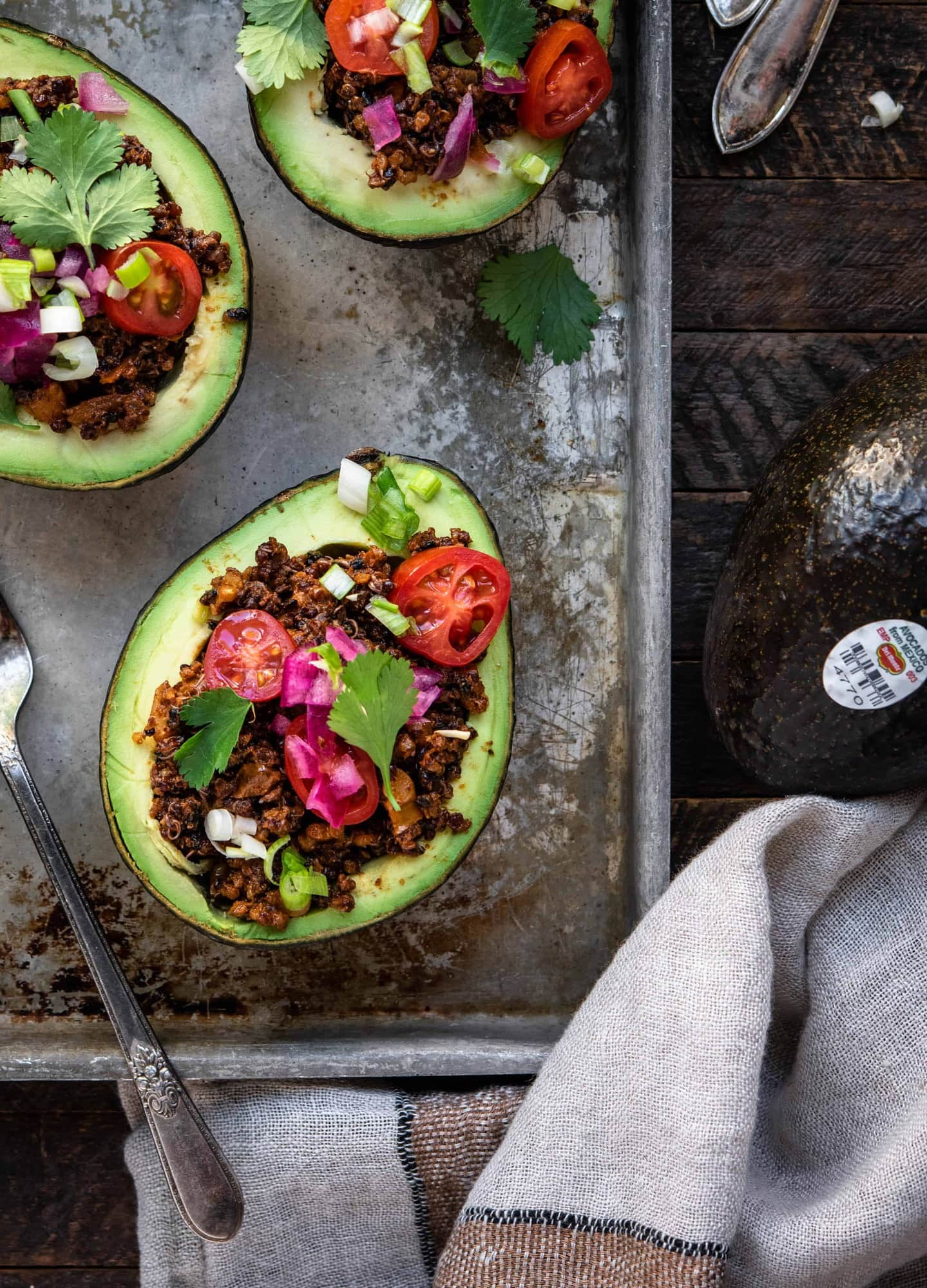 Overhead close up view of vegan taco stuffed avocados on a sheet pan on wood background