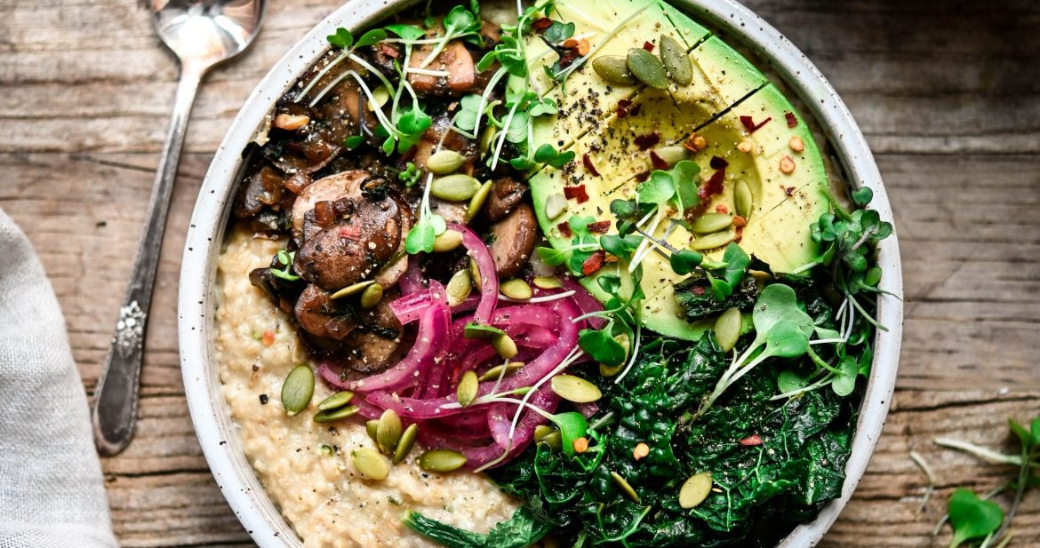 Overhead view of savory vegan oatmeal with mushrooms, kale, avocado and pickled onion in a white bowl on wood background