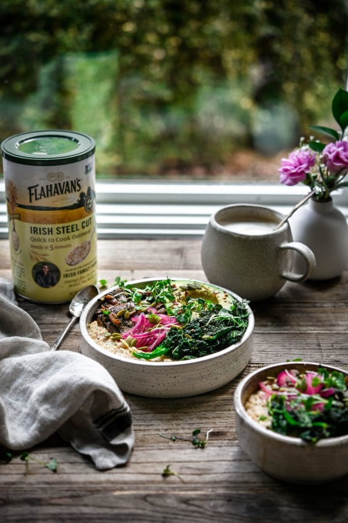 Side view of bowl of vegan savory oatmeal on a wood table with window and greenery in background