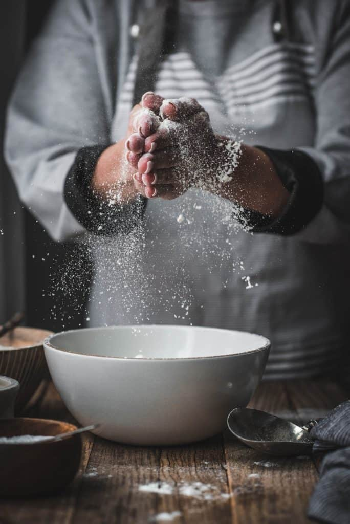 Person sifting gluten free flour from an antique sifter into white bowl on wood table