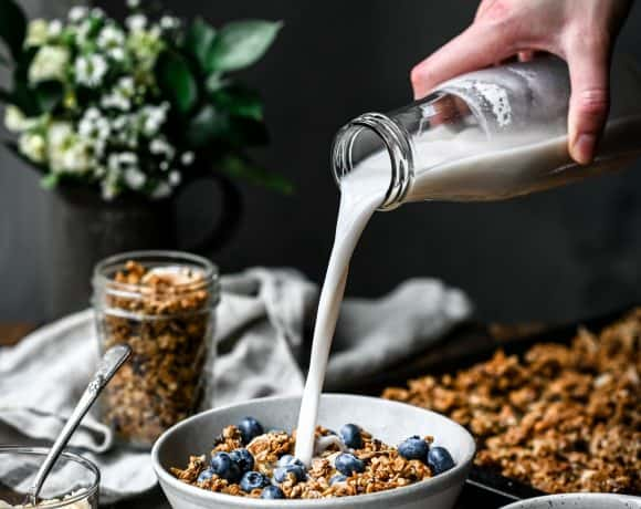 Pouring milk into a bowl of granola and blueberries on a wood table