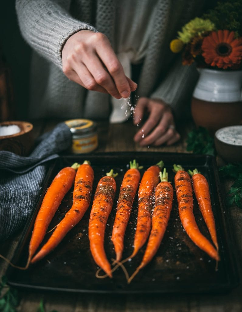 Side view of person sprinkling salt onto a tray of whole carrots on a sheet pan