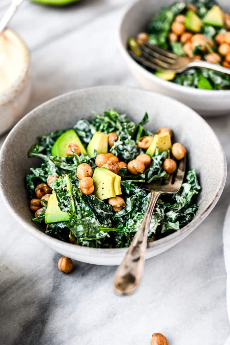 Side view of kale tahini caesar salad with crunchy chickpeas in a white bowl on marble surface