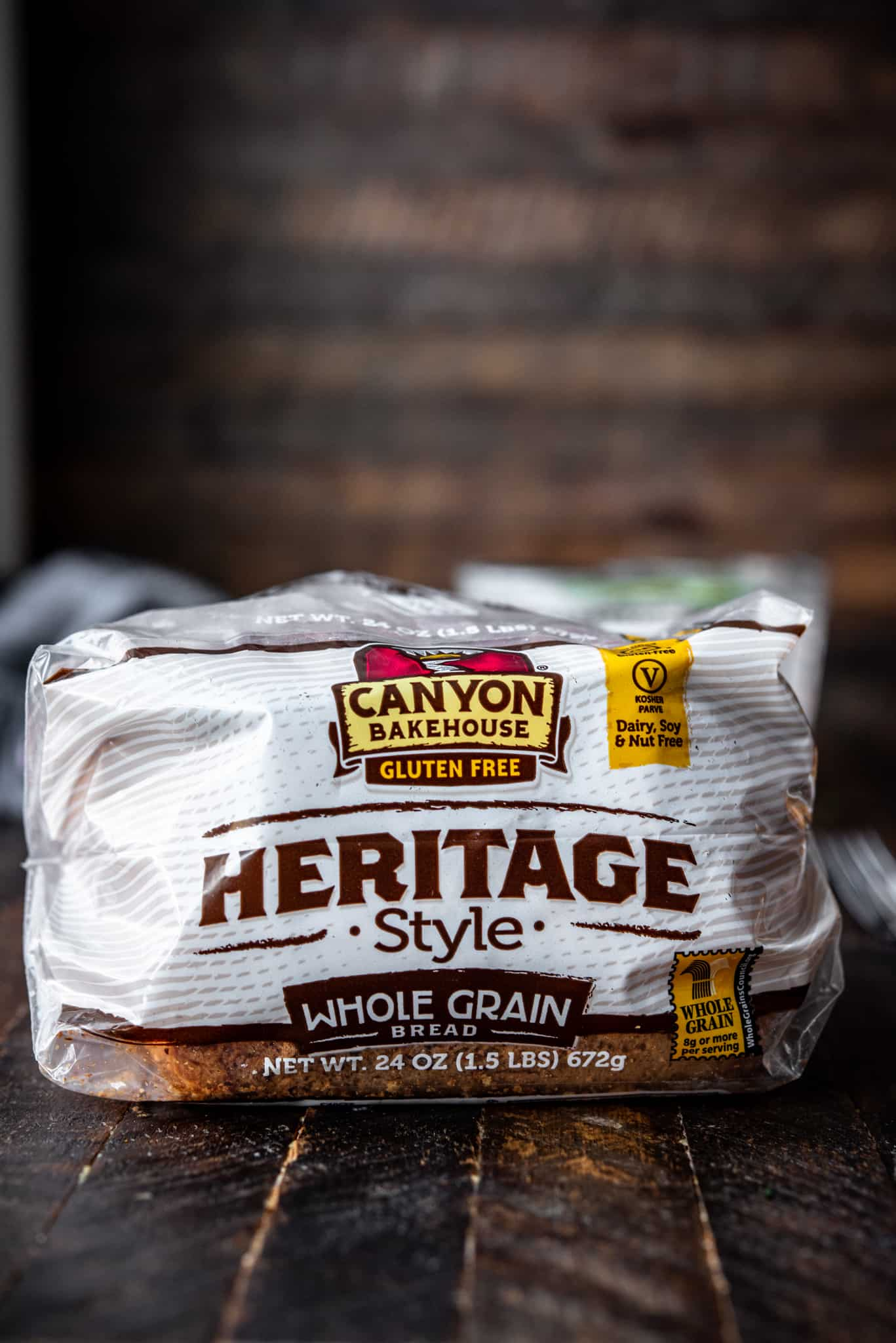 Side view of Canyon Gluten Free Heritage Style Whole Grain Bread on wood background