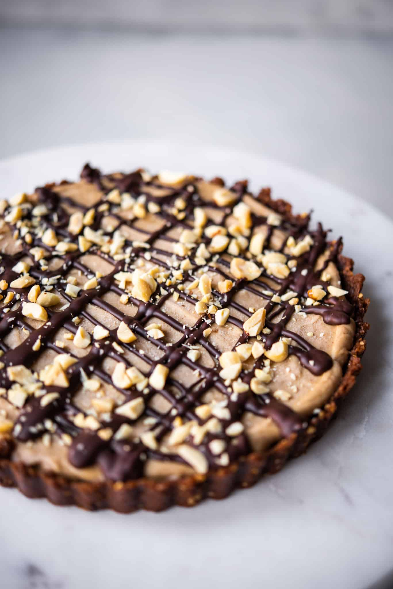 Side view of peanut butter mousse pie drizzled with dark chocolate and chopped peanuts on white background