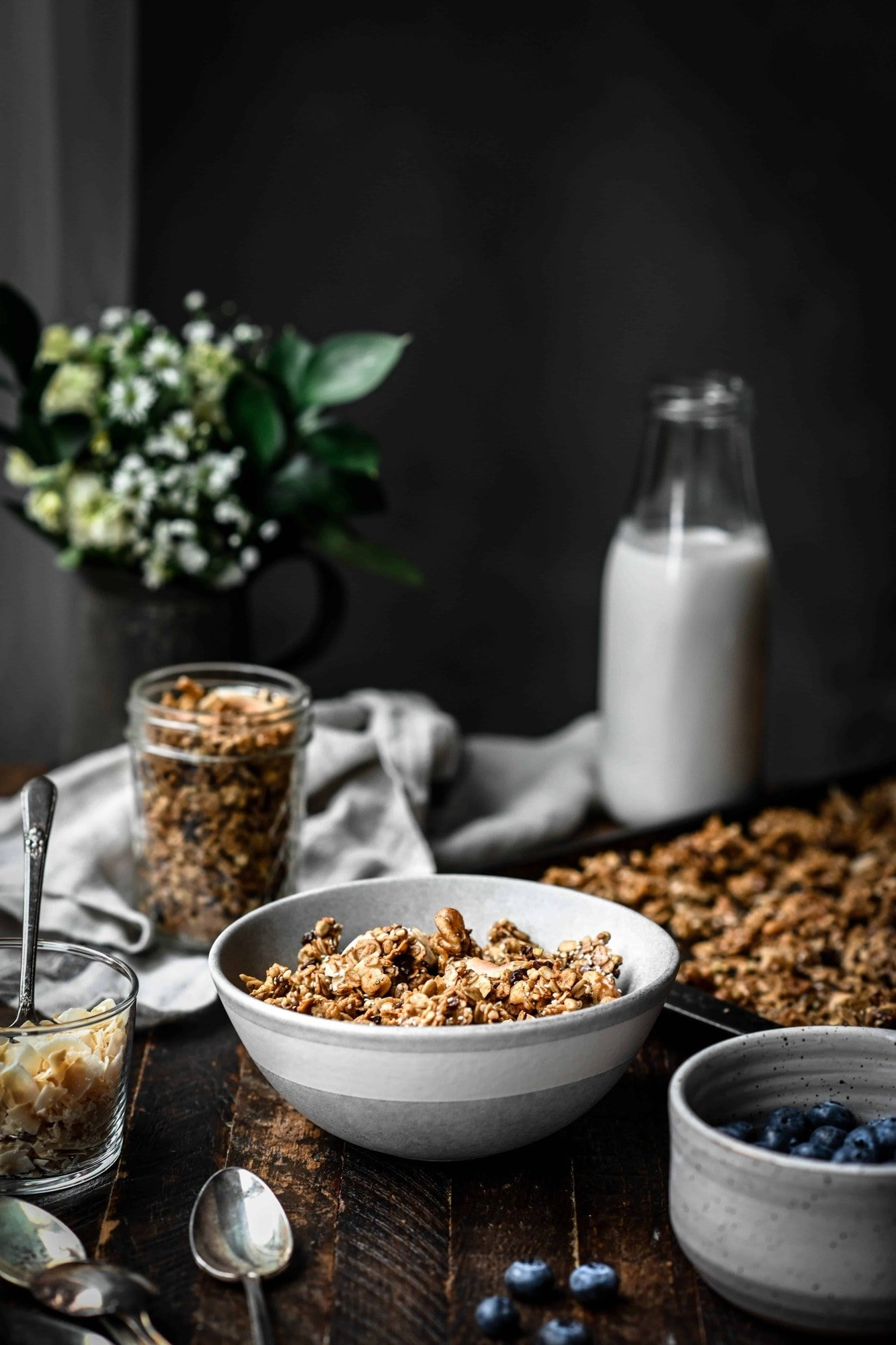 Side view of a bowl of gluten free salted caramel granola on a wood table with more granola, milk and flowers in background