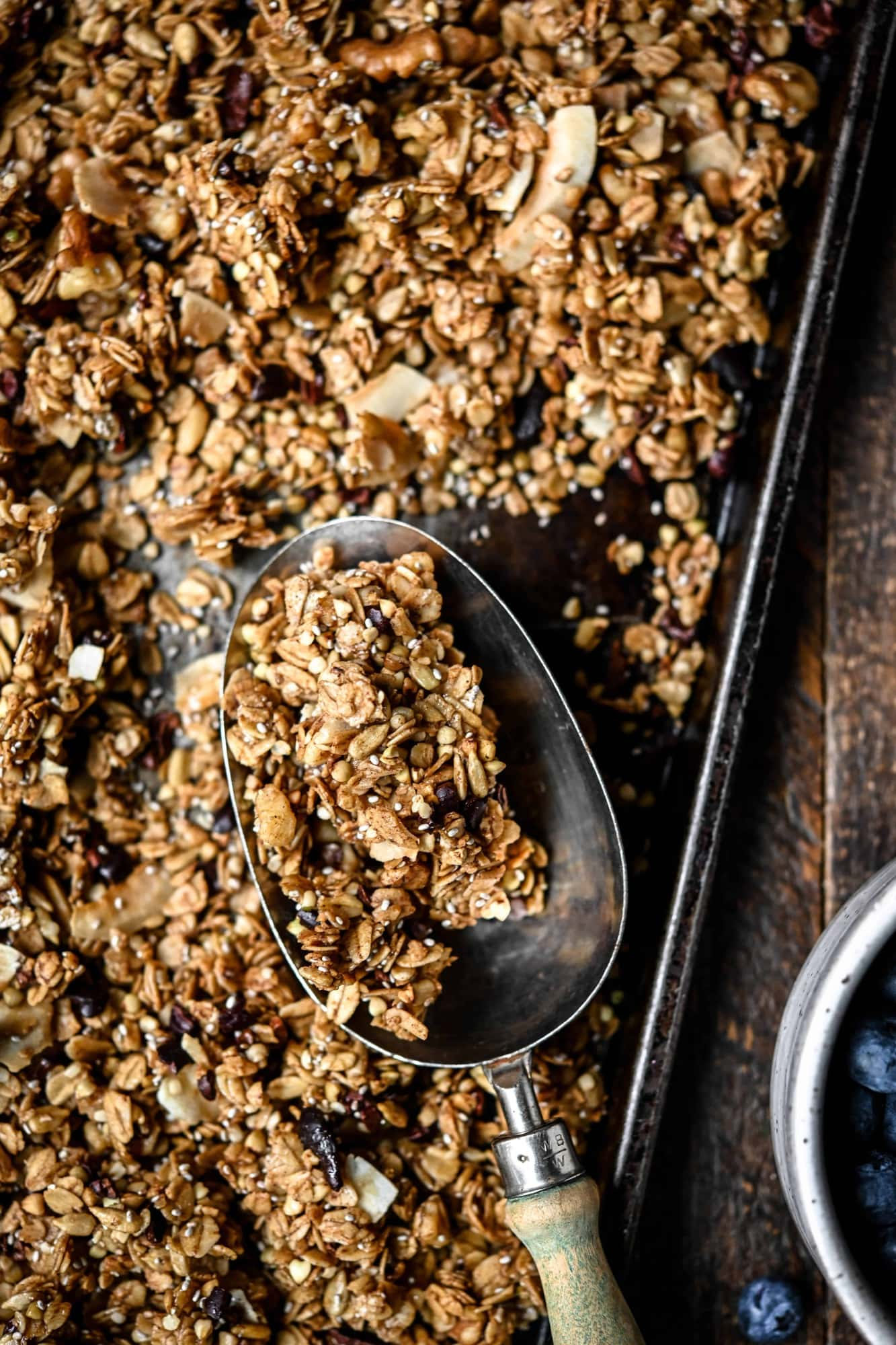 Overhead view of gluten free granola on a sheet pan, close up view of granola in a scoop