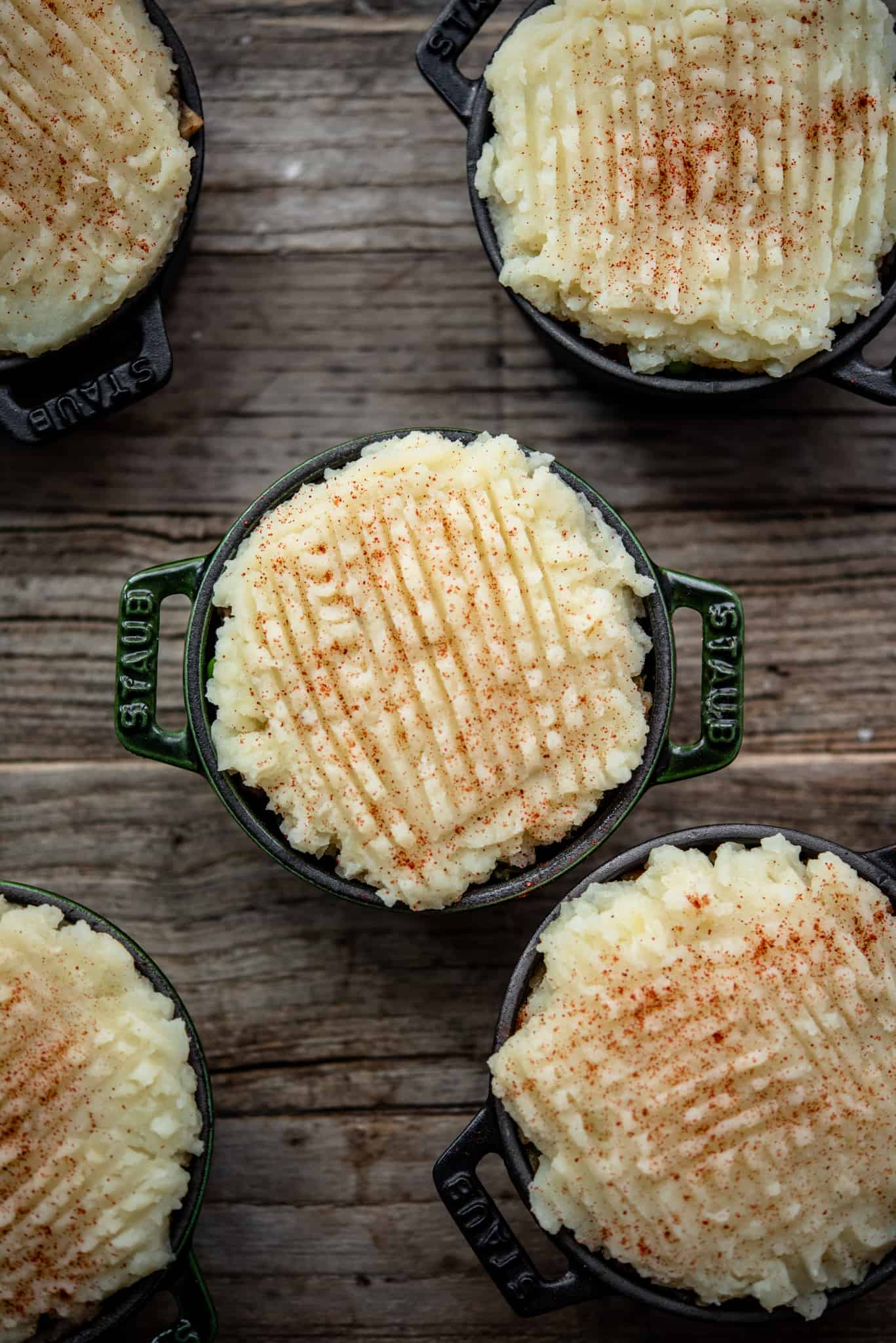 Overhead of vegan lentil shepherd's pie with mashed potatoes in mini Staub cocottes before baking