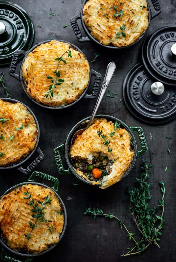 Overhead of vegan lentil shepherd's pie with mashed potatoes in mini Staub cocottes